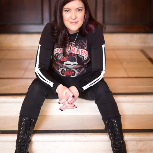 photo of punk girl Mollie Fire sitting on steps and wearing knee high combat boots, Mollie is the founder of Ink & Blood Club and is passionate about helping fiction authors be discovered and sell a million books.