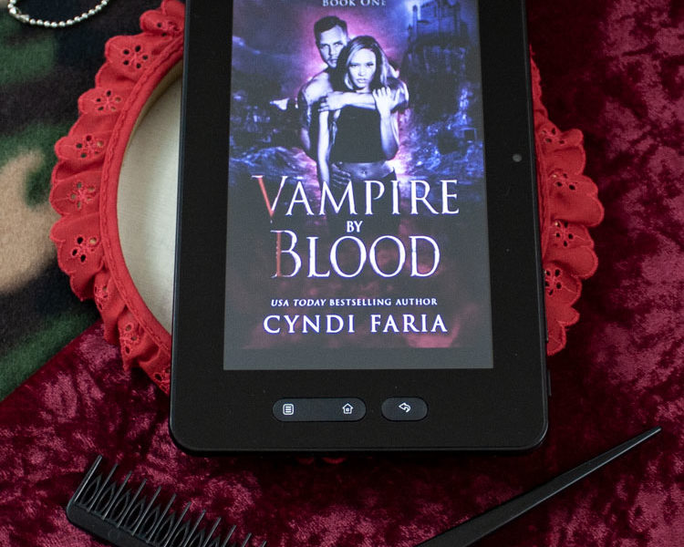 Book review of the paranormal horror fiction - Vampire By Blood - the first book in the Faeted series by Cyndi Faria - the book cover shown on a backdrop of red velvet and army camo, with military dog tags and the combs of a hairdresser in the photo.