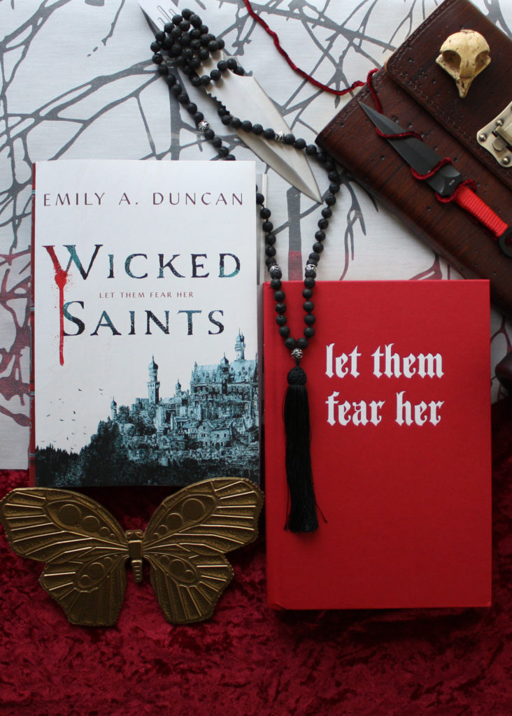 """Book review of Wicked Saints by Emily A. Duncan, a fabulously written fantasy story. Image shows the red book cover with the words """"let them fear her"""" embossed in silver letters, next to the dust sleeve cover, knives, mala beads, and other ornaments related to the book."""