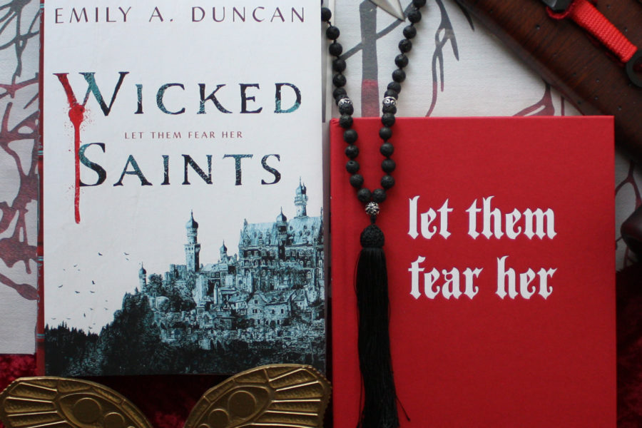 "Book review of Wicked Saints by Emily A. Duncan, a fabulously written fantasy story. Image shows the red book cover with the words ""let them fear her"" embossed in silver letters, next to the dust sleeve cover, knives, mala beads, and other ornaments related to the book."