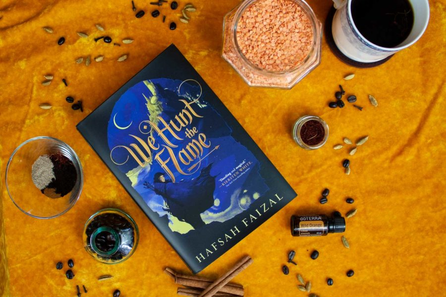 The spices, foods, and smells straight out of We Hunt The Flame book by Hafsah Faizal. Photo shows the book laying on a background of yellow velvet, surrounded by red lentils, cinnamon sticks, cardamom seeds, saffron, coffee beans, orange essential oil, and a mug of qahwa. #book-hangover #recipes #fantasy-fiction